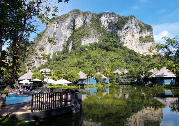 Individual cottages amongst lagoon with limestone mountain in the background at the Peace Laguna Resort