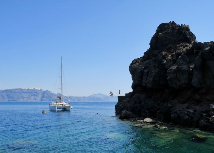 Swimming and cliff jumping on Santorini boat tour.