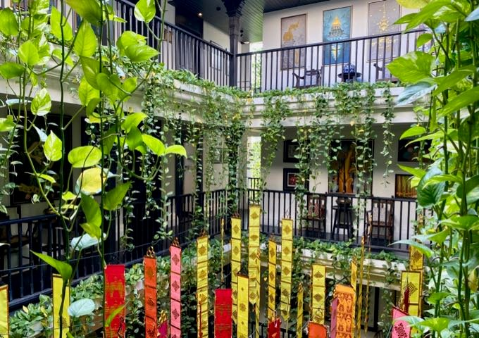 Elegant Thai hotel courtyard with hanging plants and colorful banners
