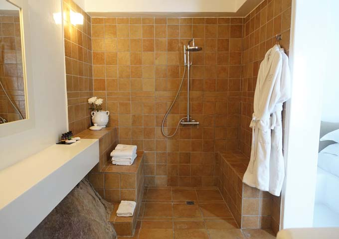 The bathroom features a large Greek shower.