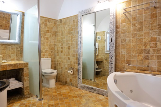 The tiled bathroom is very spacious and bright.