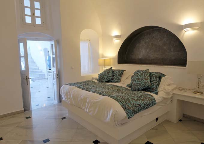 The bedroom is spacious and has a king bed and marble floor.