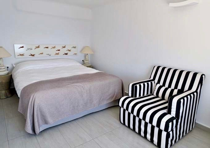 The bedroom on the upper floor has a queen bed and a small couch.