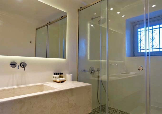 The second bathroom also features marble and glass.