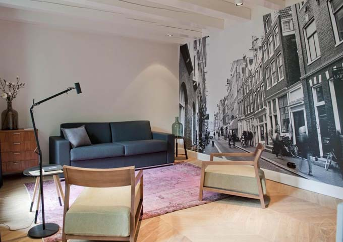 The Huidenstraat suite's living area has a wall-length print of Amsterdam.