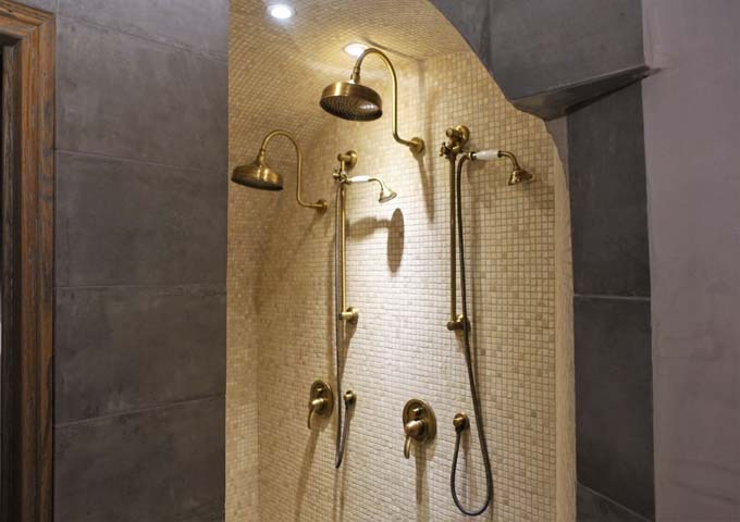 The bathroom has twin antiqued brass showers.