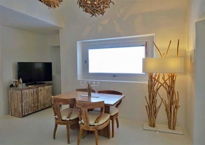 The dining area features a cozy wooden table for 4.
