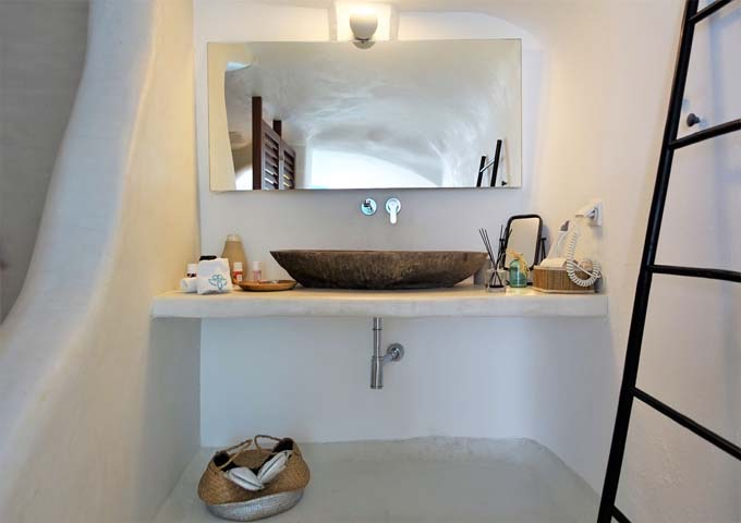 The bathroom has a cave-style shower and rock sink.
