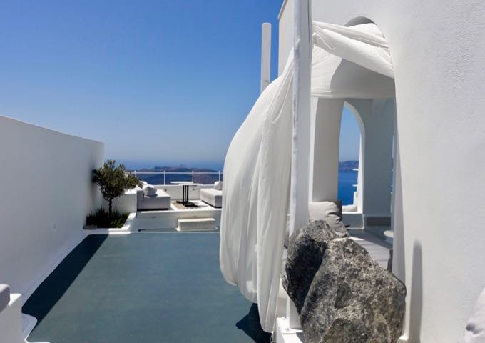 The hotel features a Cycladic design with exposed rocks.