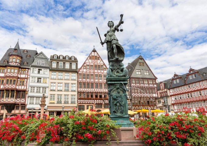 Statue of a woman holding scales in the middle of a Bavarian old town square