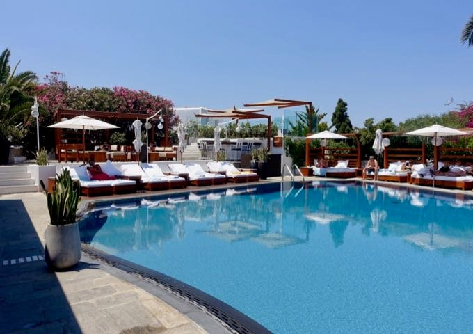 The pool deck features sun loungers, Bali beds, and a dining area.
