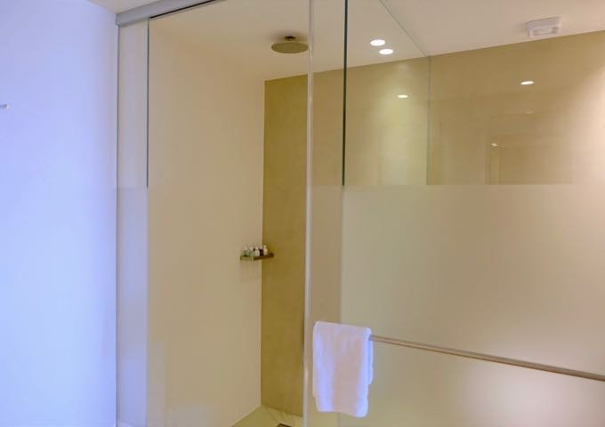 The bathroom also features a glass shower with a rainfall showerhead.