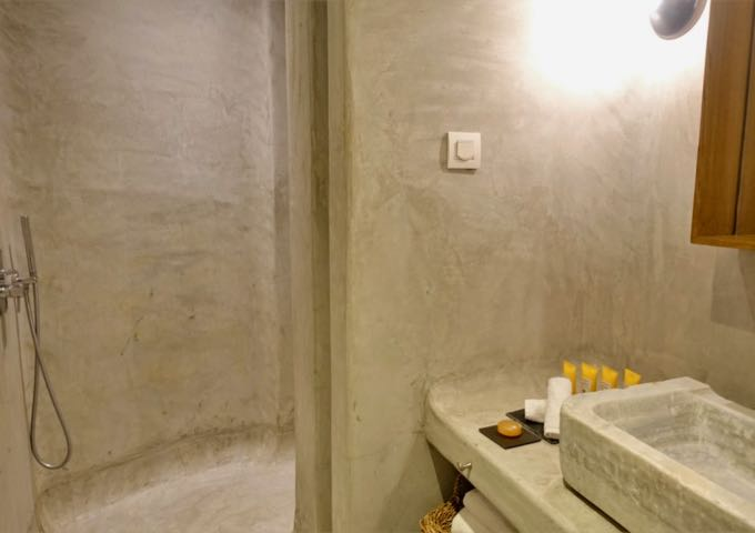 The Bohemian Suite's bathroom comes with a Greek-style open shower, pressed concrete, and antique marble sink.