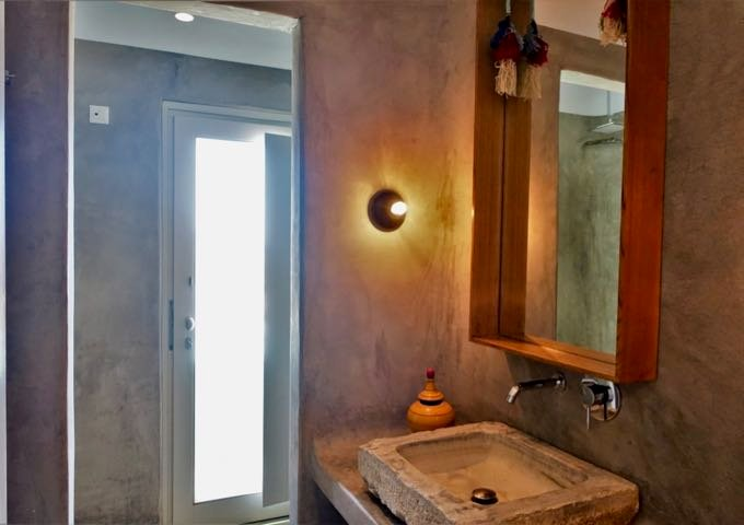 The suite's bathroom has pressed concrete, open shower with a window, and an antique sink.