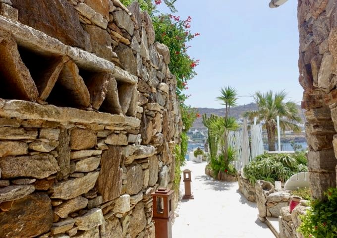 A path between classic Mykonian style walls leads to the pools, beach, spa, and restaurant.