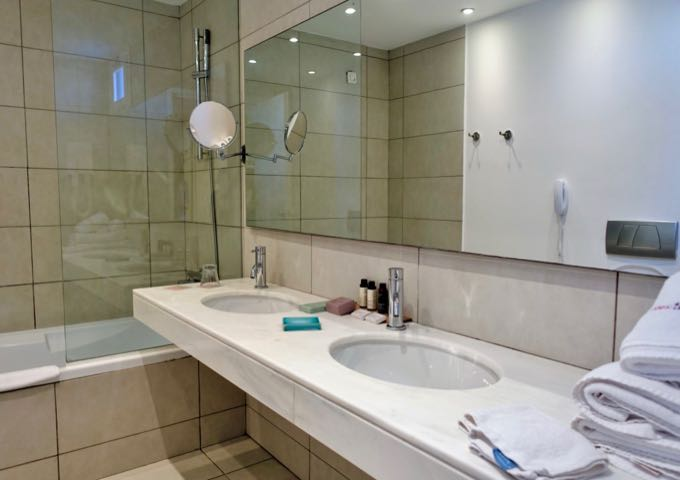 The spacious bathroom has a shower/tub combo and dual vanities.