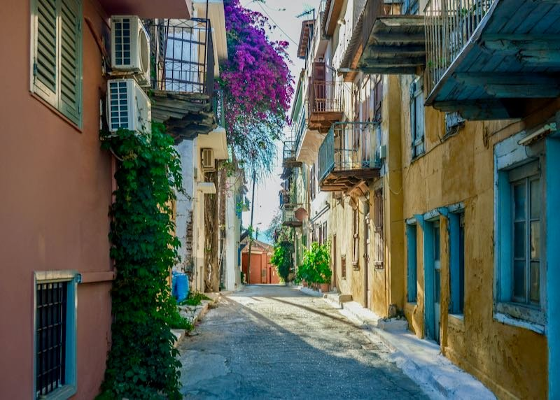 Narrow stone walkway lined with colorfully-painted buildings with flower-draped balconies