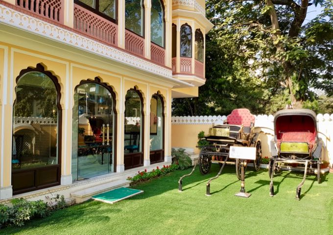 The hotel lawn showcases 2 old horse buggies.