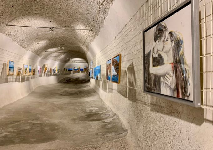 Long cave tunnel with artwork displayed along the walls