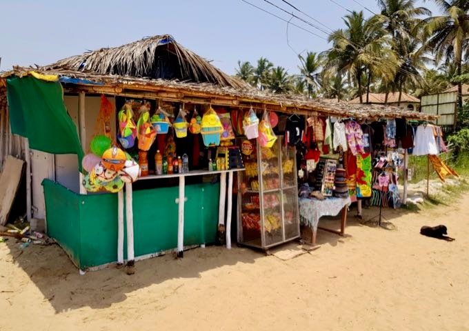 A few stalls sell souvenirs and beach gear on the sand.