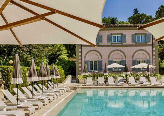 Swimming pool surrounded by loungers and umbrellas, set in back of a Florentine Villa