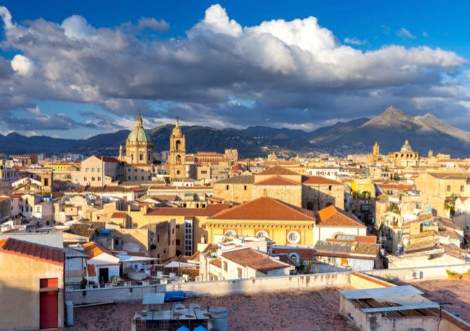Aerial shot of rooftops and Palermo Cathedral, with mountains in the distance