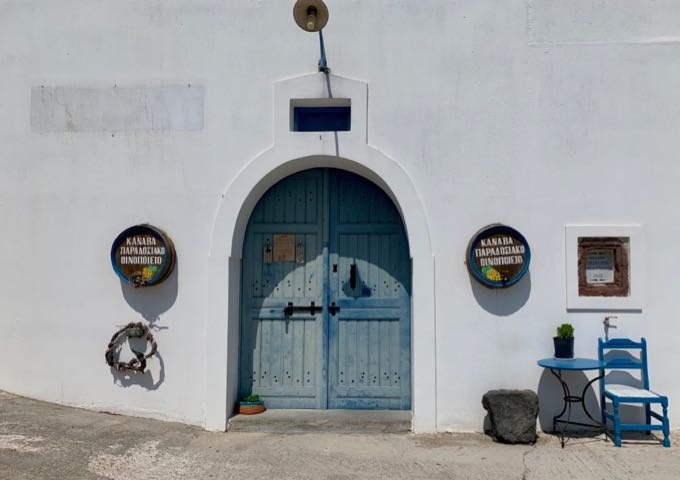 Arched blue doorway in a white stucco building, with wine barrels to either side.