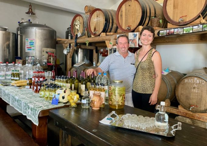 Couple smiling in front of a table of homemade goods, in front of a wall of wine barrels.