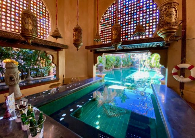 Indoor-outdoor swimming pool with a swim-up bar, surrounded by hanging lanterns