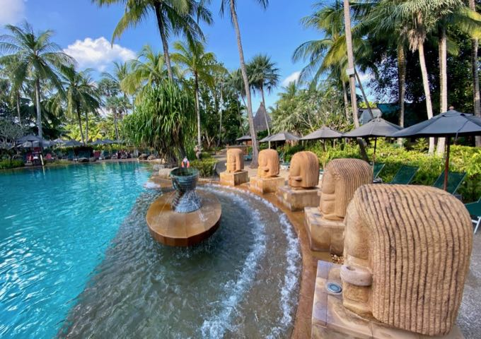 Beautiful swimming pool surrounded by statues and palm trees