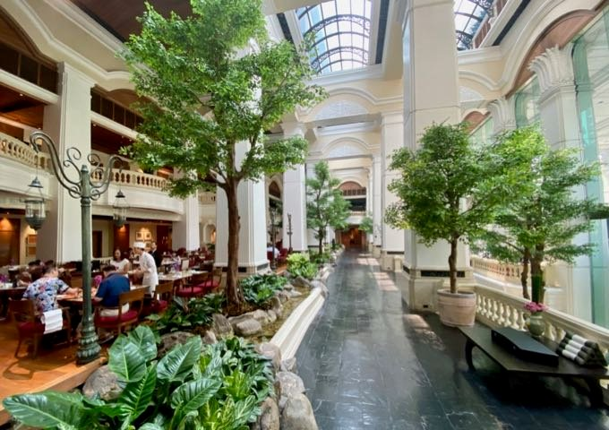 Elegant hotel lobby with skylights, trees, and adjacent fine dining restaurant