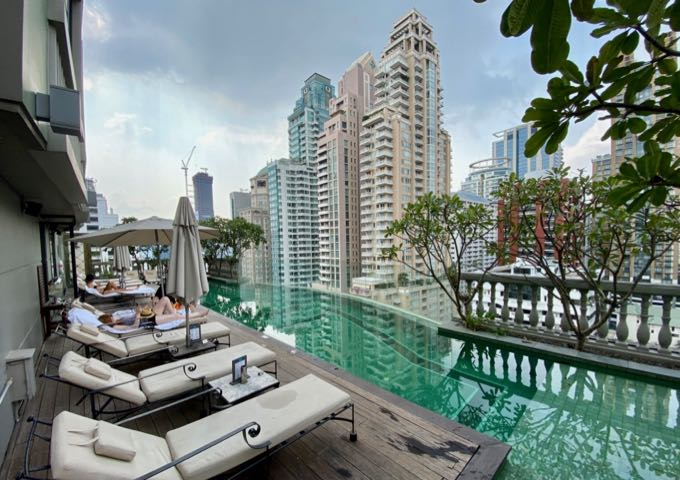 Hotel rooftop swimming pool with elegant chaise lounge chairs, set amid the Bangkok skyscrapers