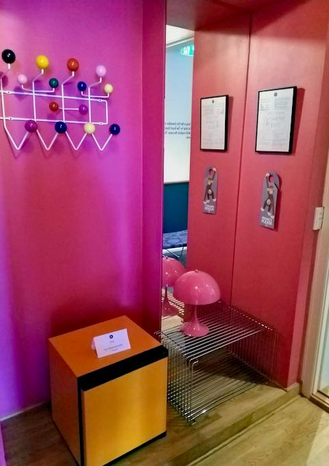 A candy pink hallway connects the orange lounge to the blue bedroom.