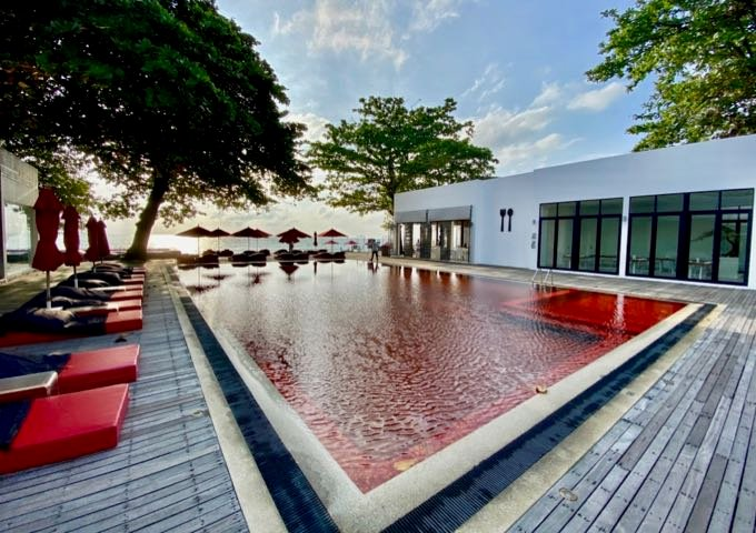Umbrella-lined swimming pool whose water appears red, due to being lined with red-colored tiles