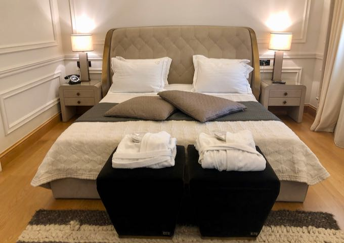 Luxury hotel bed with upholstered headboard, flanked by side tables with crystal lampsd