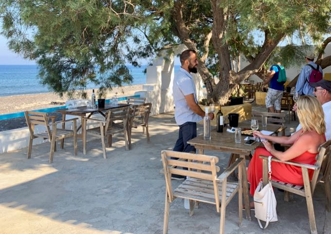 A waiter serves food and wine to a man and a woman on a patio