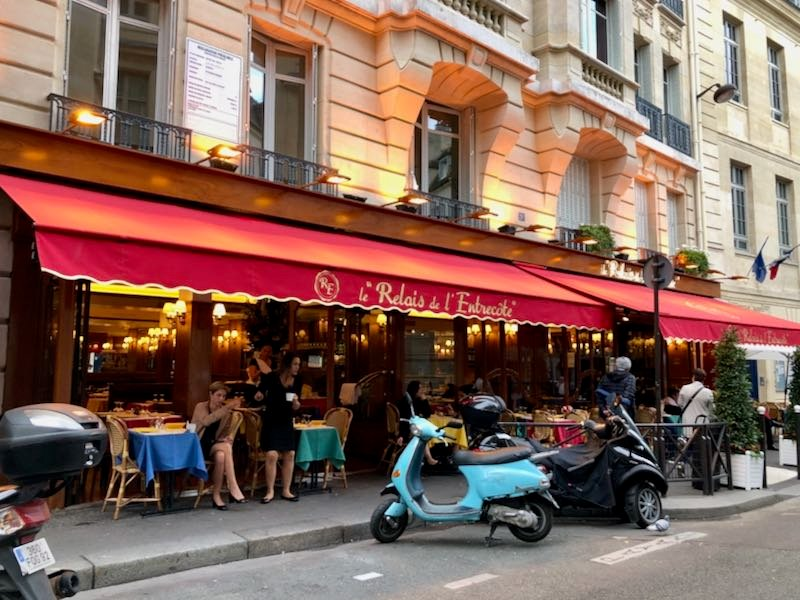 Exterior shot of a Paris bistro with Vespas in the foreground