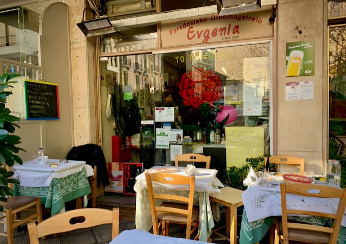 sidewalk tables in front of a cafe window, set for lunch service