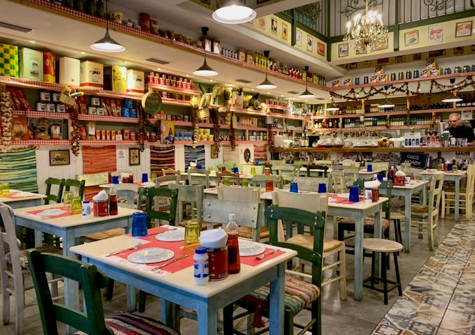 Restaurant tables in a large room lined with colorful items for sale