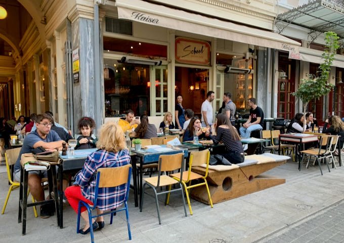 Sidewalk tables in front of a pizzaria, with one bench in the shape of a clothespin