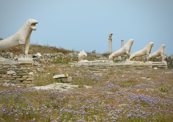 Stone lion statues, surrounded by wildflowers