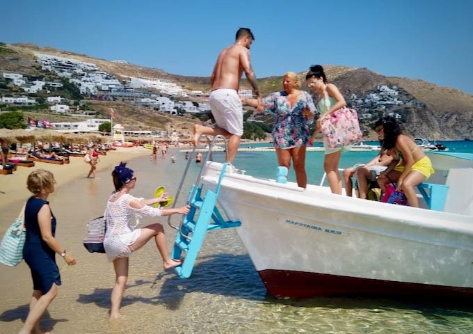 Passengers climb a ladder to board a water taxi from a beach