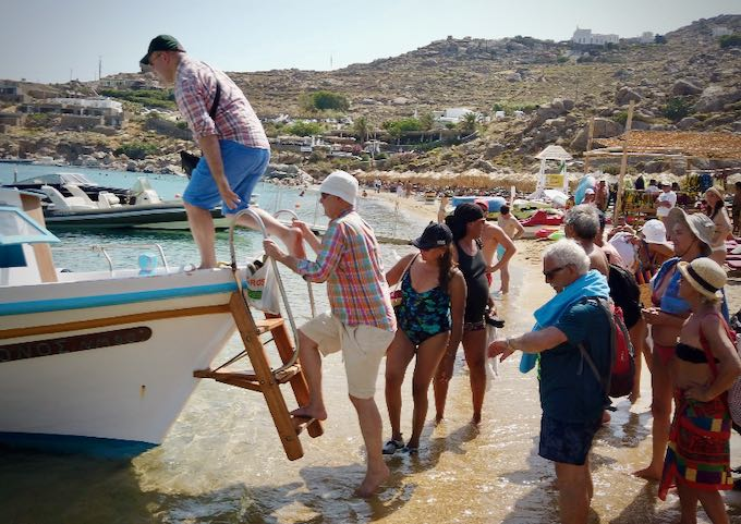 Passengers climb a ladder to board a water taxi boat on a sandy beach