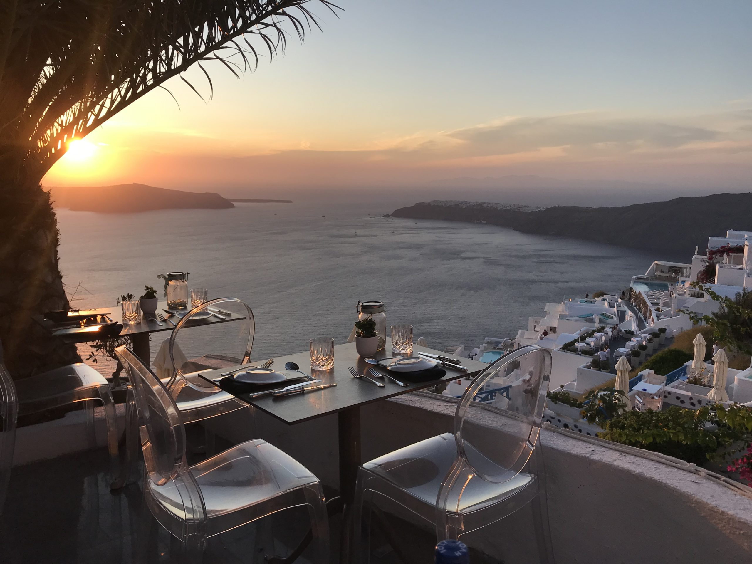 Sunset view of the Santorini caldera from a table set at Athenian House restaurant in Imerovigli