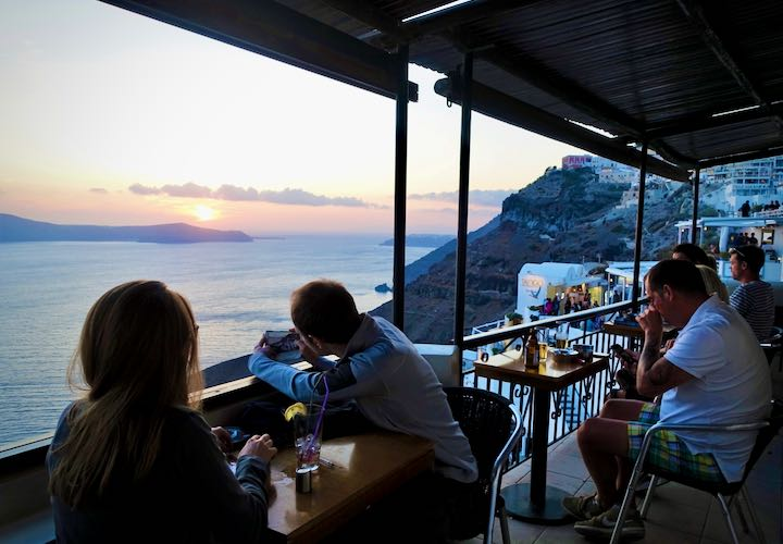 Couples at a bar on Santorini, watching the sunset