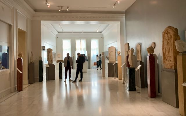 People admire ancient Greek artifacts in an airy gallery space