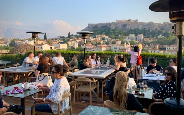 Diners and tourists at a rooftop bar with a view of the Acropolis