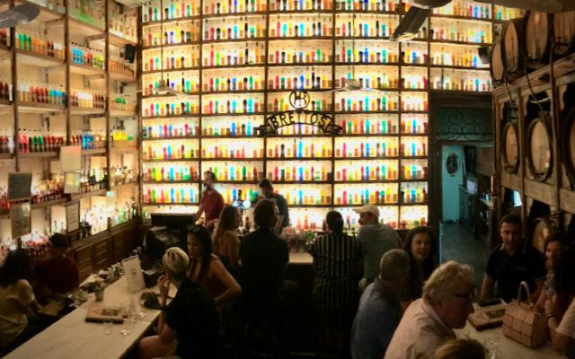 An illuminated wall lined with coloful bottles behind a wooden bar.