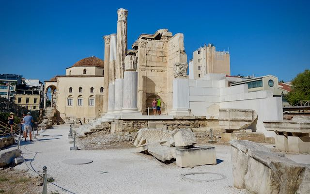 Tourists pose for a photo in the ruins of Hadrian's Library in Athens