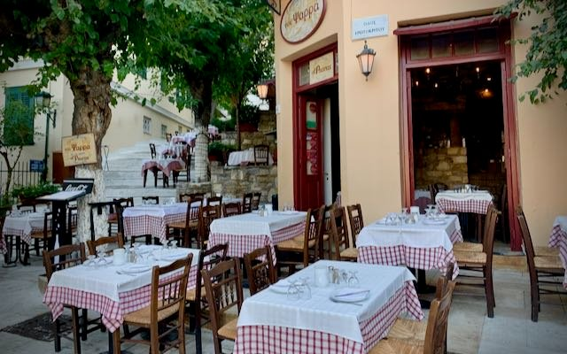 Tables set for outdoor diners at a Greek taverna in Athens